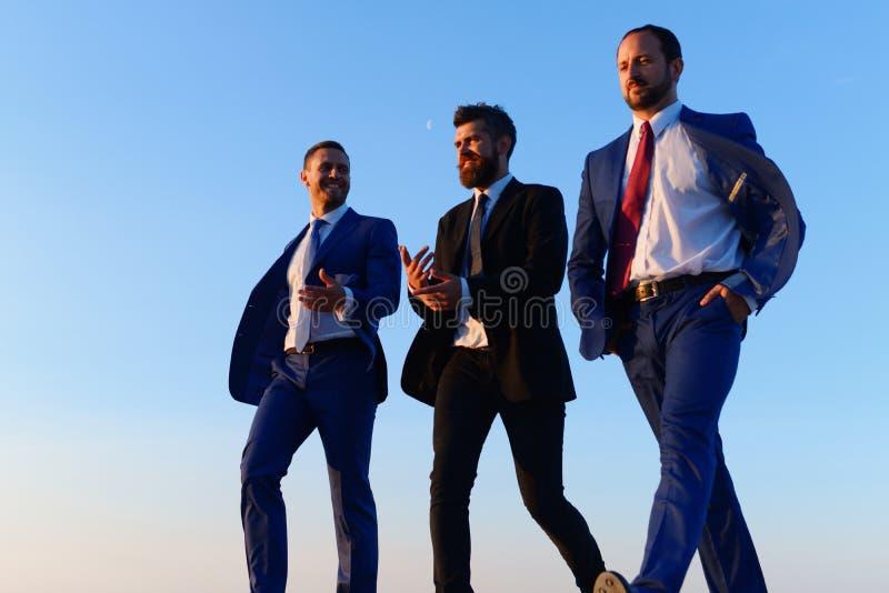 De bedrijfleiders nemen een gang op de achtergrond van de zonsonderganghemel royalty-vrije stock fotografie