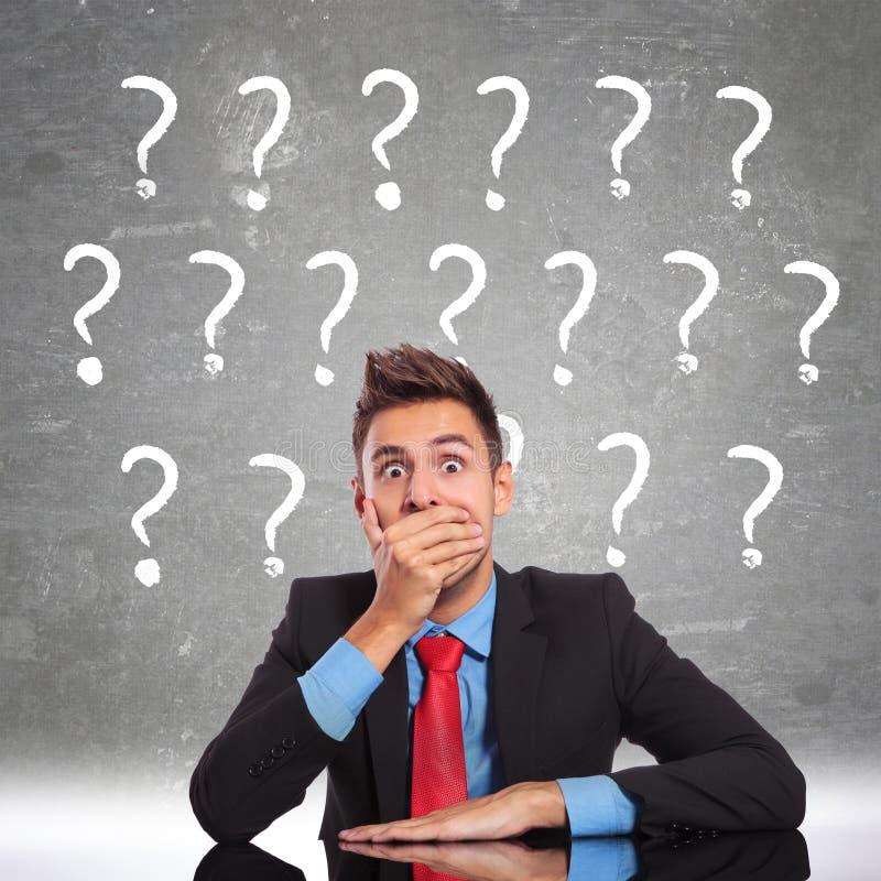 De bedrijfs mens die shoked door alle vragen kijkt stock afbeelding
