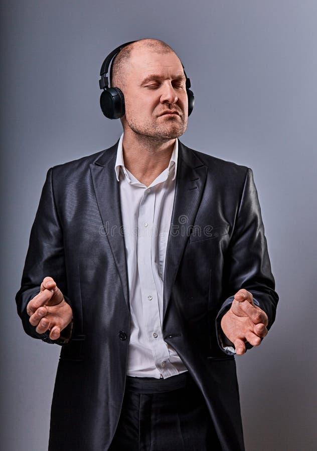 De bedrijfs de muziek in draadloze oortelefoon en mens die ontspant hij die het teken van de handenyoga zen op grijze studio tone royalty-vrije stock foto