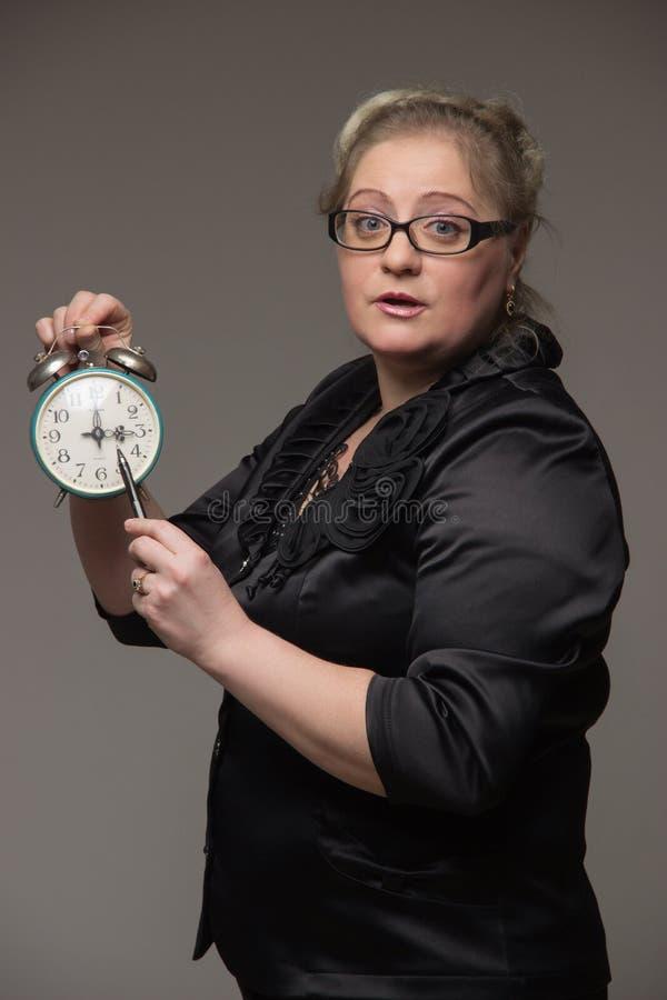 De bedrijfs vette vrouw met een klok wijst erop dat de tijd is gekomen stock foto