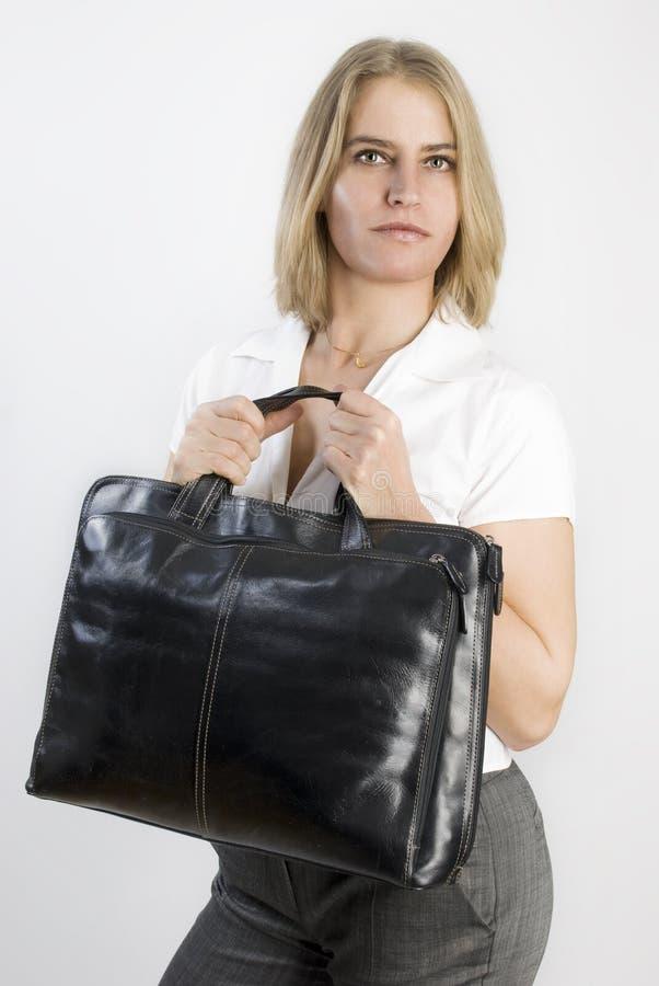 De bedrijfs vrouw met aback doet in haar handen in zakken. stock fotografie