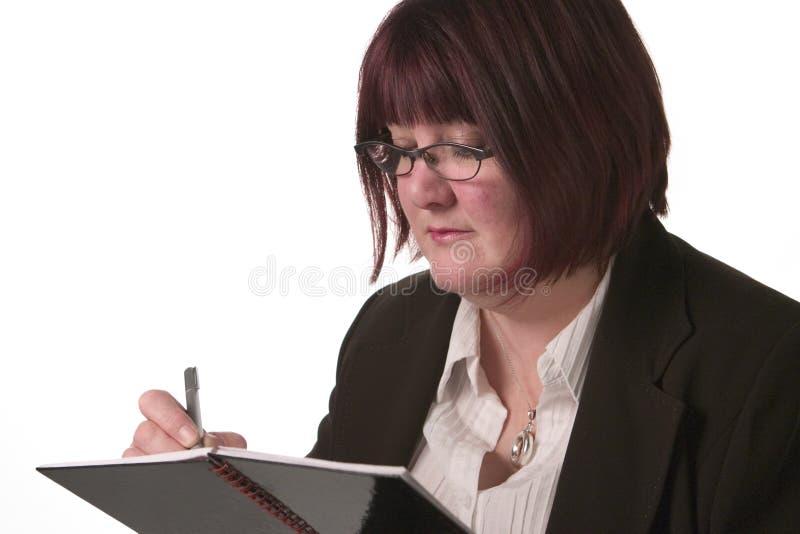 De bedrijfs vrouw schrijft in agenda stock foto