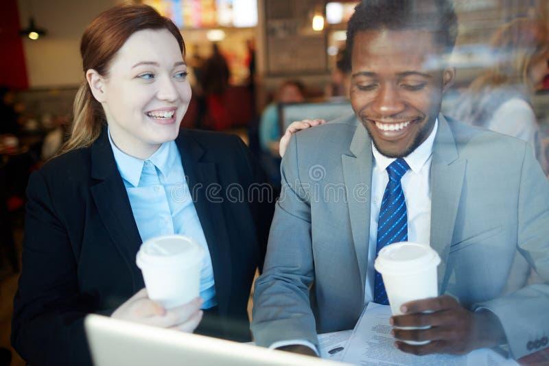 De bedrijfscollega's die in Koffie lachen winkelen na het Werk stock afbeeldingen