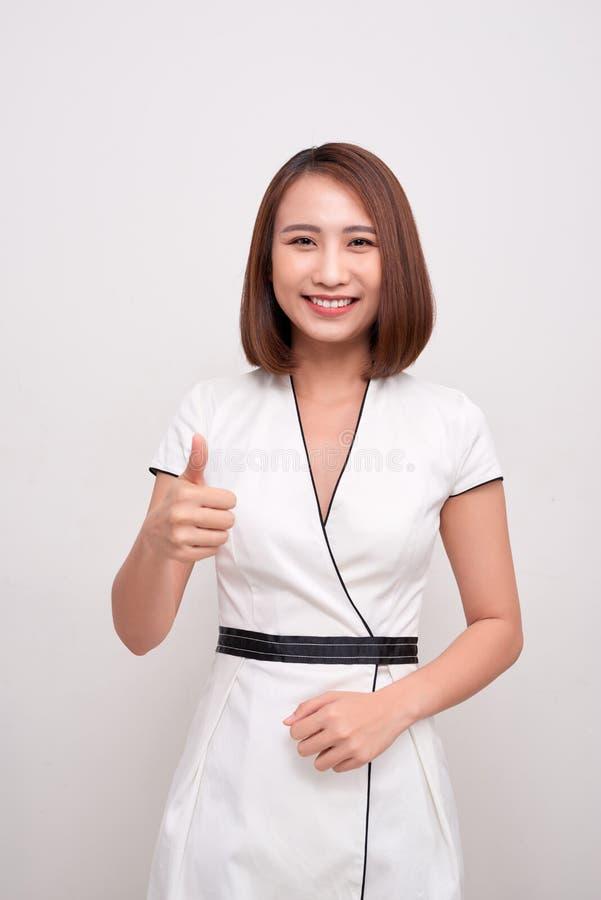 De bedrijfsdievrouw toont duim omhoog op witte achtergrond, Aziatische schoonheid wordt ge?soleerd stock foto