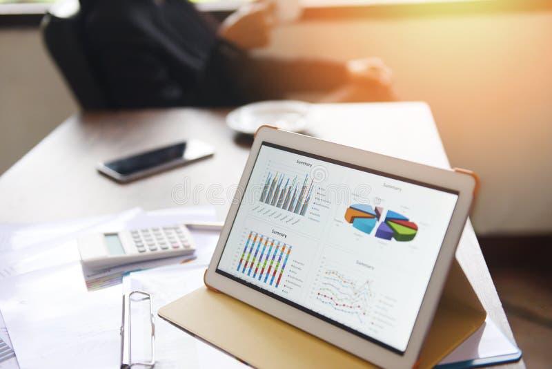 De bedrijfsgrafieken brengen op een tabletcomputertechnologie in kaart op de lijst en de vrouw die in bureau met koffiekop werken stock foto