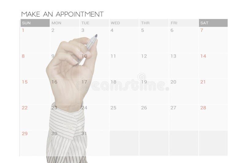 De bedrijfshand doet een benoeming op de vergadering van de kalenderontwerper stock fotografie
