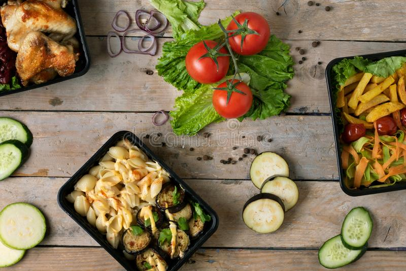 De bedrijfslunch in voedseldozen, de vleugels van de braadstukkip, stoomde groenten, gestoofd vlees, klaar te eten maaltijd royalty-vrije stock afbeelding