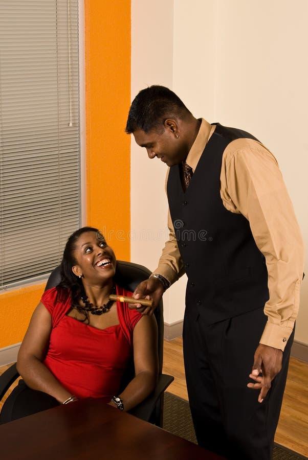 De bedrijfsman biedt zijn Bedrijfsvrouw een Sigaar aan stock fotografie