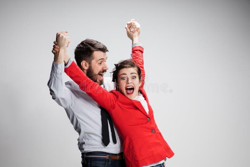 De bedrijfsman en de vrouw die op een grijze achtergrond lachen royalty-vrije stock fotografie