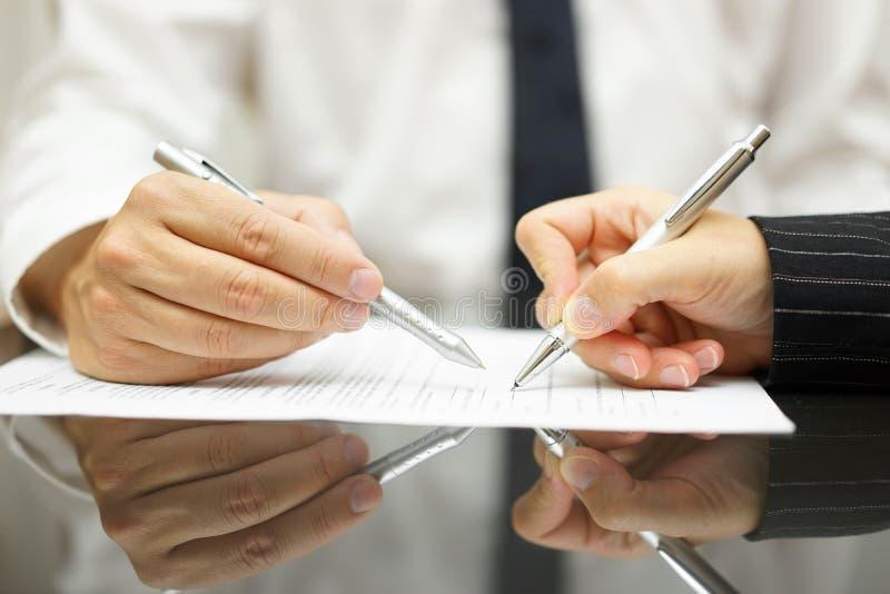 De bedrijfsman toont met pen aan bedrijfsvrouw waar te ondertekenen royalty-vrije stock afbeelding