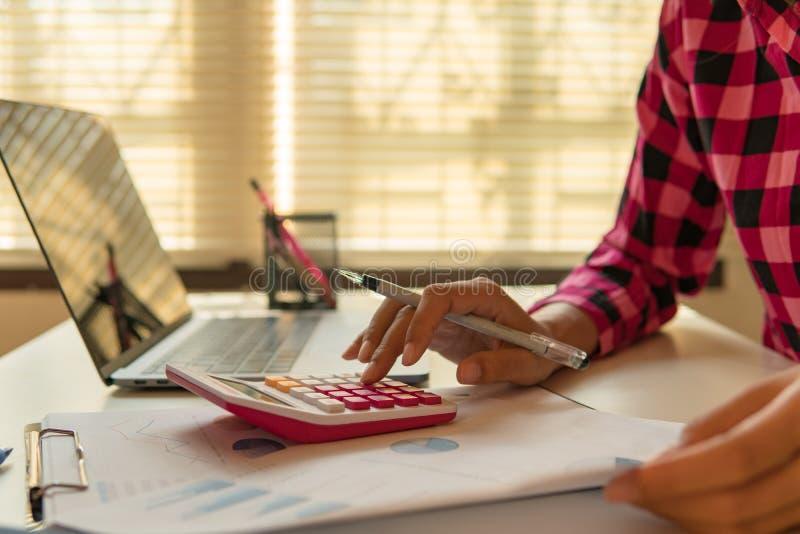 De bedrijfsmens berekent over kosten en het doen van financiën op kantoor royalty-vrije stock fotografie