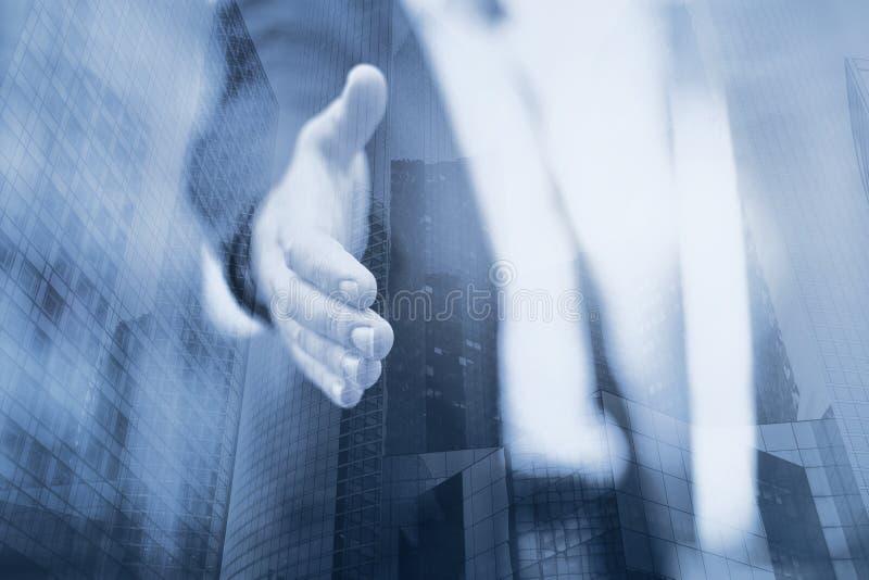 De bedrijfsmens biedt een overeenkomst of een hulp, handdruk, dubbele blootstelling aan royalty-vrije stock fotografie