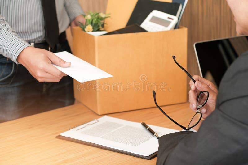 De bedrijfsmens die berustingsbrief verzenden naar werkgever en Holdingsmateriaal treedt indrukt of dragend kartonvakje door bure royalty-vrije stock fotografie