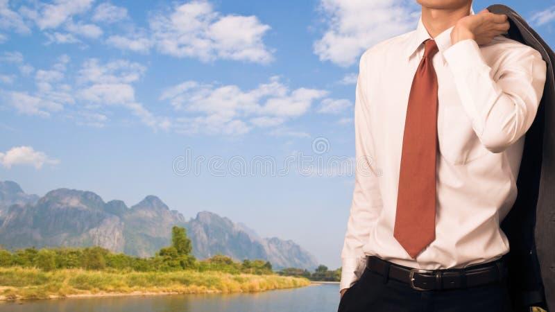 De bedrijfsmens die zijn kostuumjasje op zijn schouder houden, ontspant conc royalty-vrije stock afbeeldingen