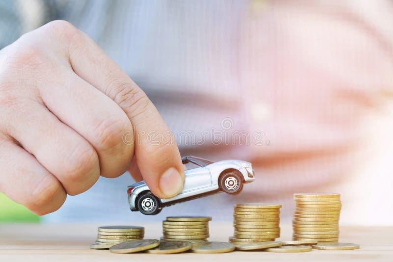 De bedrijfsmens en sluit omhoog het model van de handholding van stuk speelgoed auto op over een geld van gestapelde muntstukken  royalty-vrije stock afbeelding