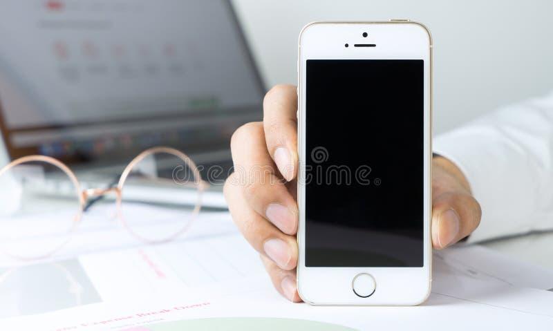 De bedrijfsmens gebruikt iphone voor zijn zaken stock afbeelding