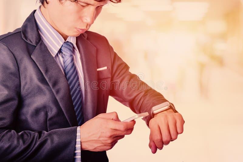 De bedrijfsmens gebruikt mobiele telefoon en slim horloge stock afbeelding
