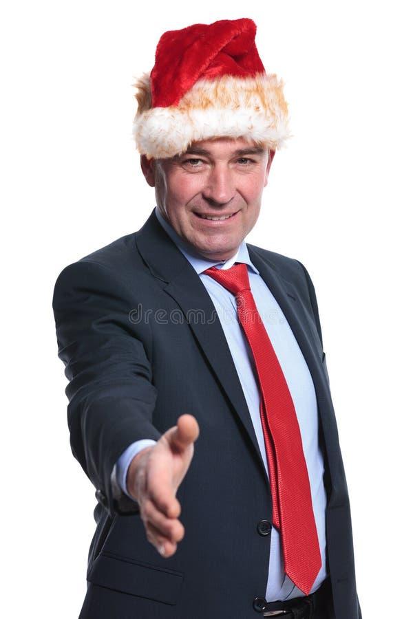 De bedrijfsmens in Kerstmishoed heet u met een handschok welkom stock afbeelding