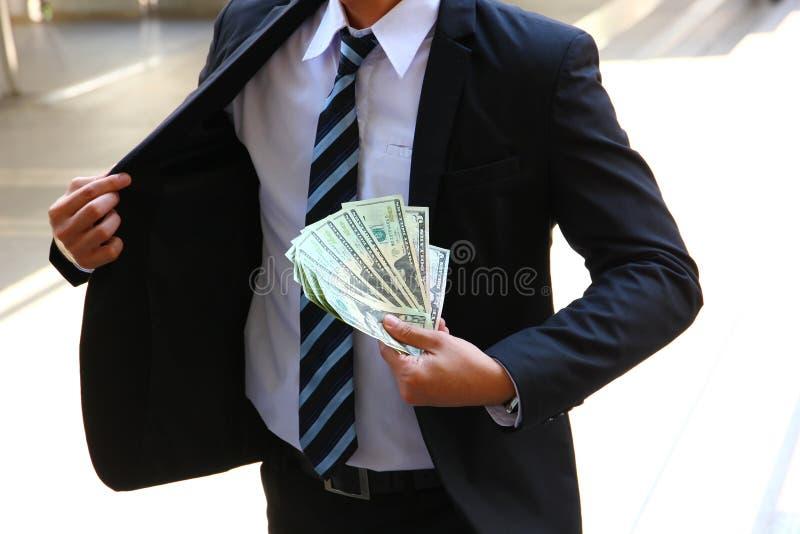 De bedrijfsmens in kostuum toont zijn dollars in zijn hand stock afbeeldingen