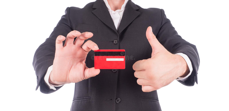 De bedrijfsmens in Kostuums toont duim en holding leeg wit die creditcardmodel op witte achtergrond wordt geïsoleerd met royalty-vrije stock foto