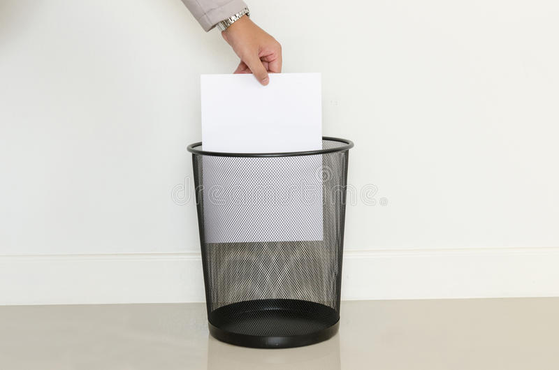 De bedrijfsmens laat vallen binnen een nutteloos document aan het afval stock afbeeldingen