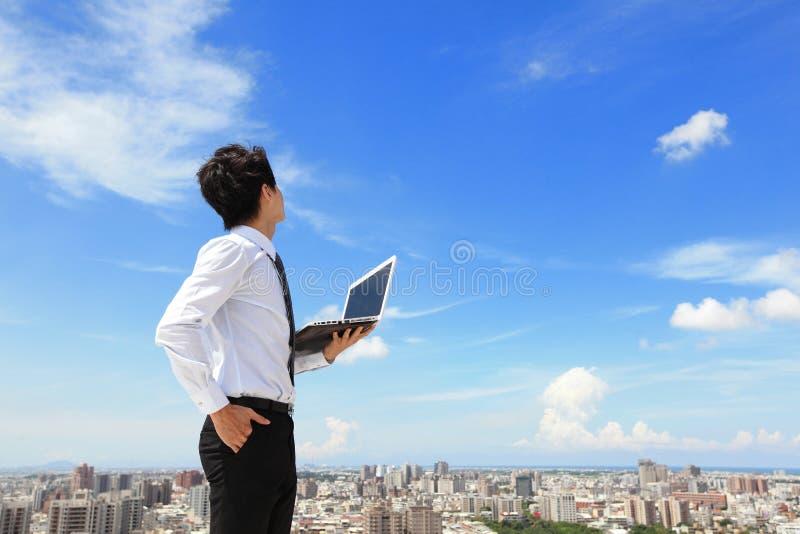 De bedrijfsmens met laptop en kijkt hemel en wolk stock foto