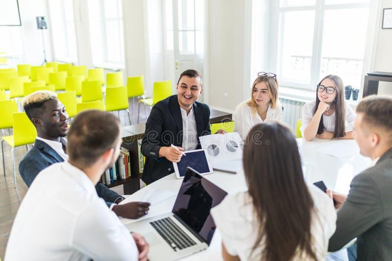 De bedrijfsmens op kantoor met laptop werken en de documenten die introduceren de resultaten van project aan team De Eenheid van  stock afbeeldingen