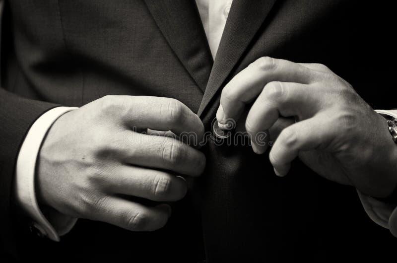 De bedrijfsmens ruimt de knoop van zijn kostuum op, maakt een keurig beeld stock foto