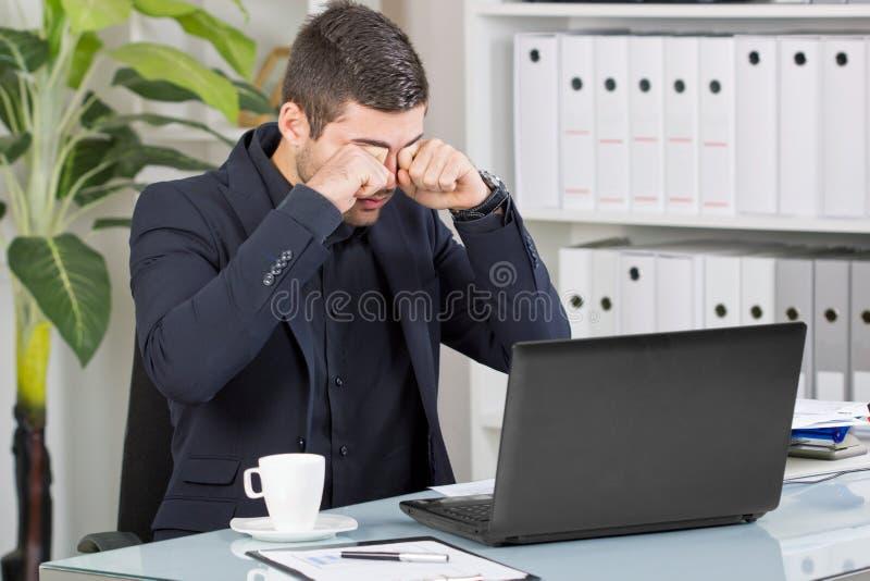 De bedrijfsmens wrijft zijn ogen van het slechte nieuws op het kantoor stock afbeelding