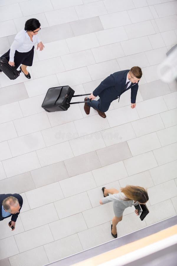 De bedrijfsmensen die met aktentassen in bureau lopen lobbyen royalty-vrije stock fotografie