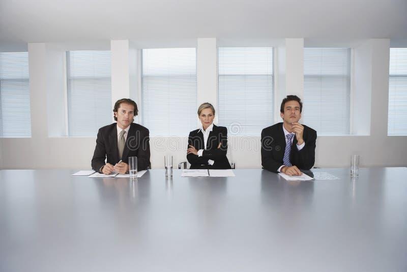 De bedrijfsmensen die op Conferentie zitten dienen in stock foto