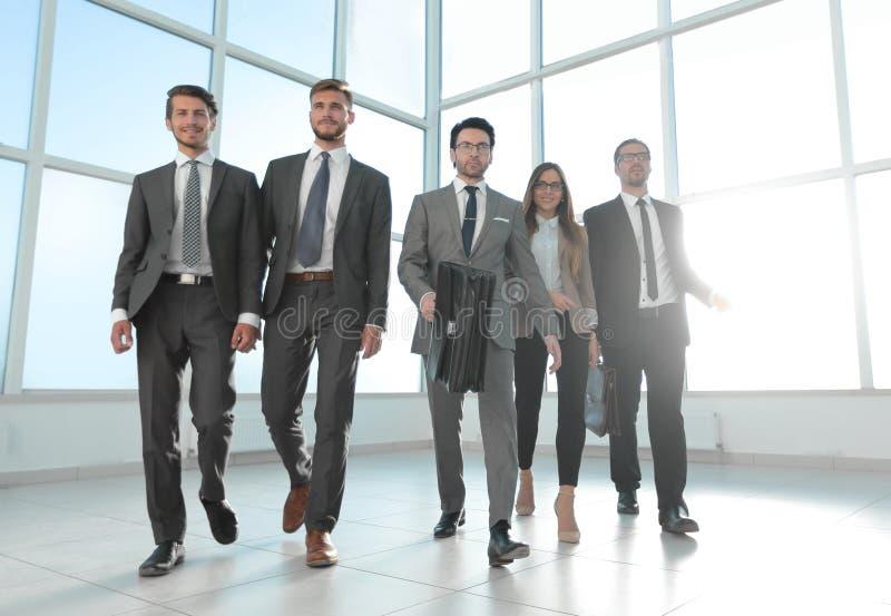 De bedrijfsmensen gaan onderaan de gang van een modern bureau stock afbeelding