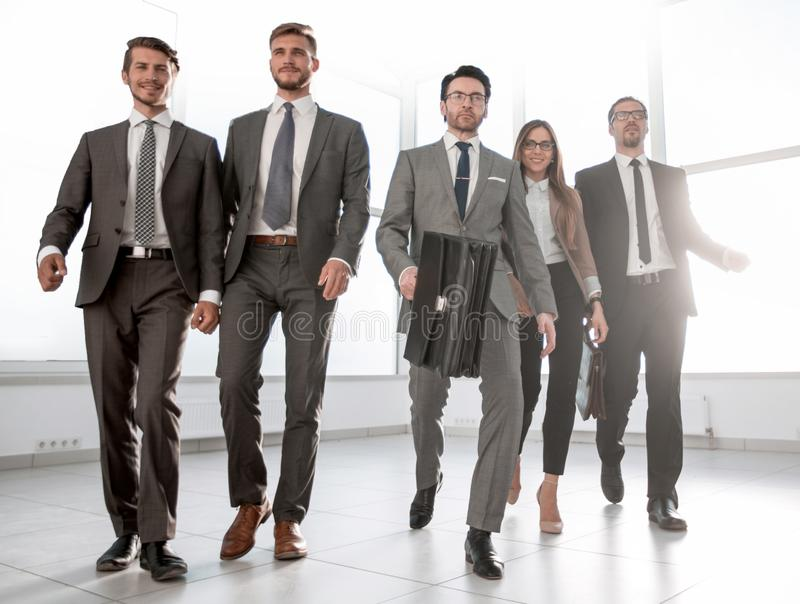 De bedrijfsmensen gaan onderaan de gang van een modern bureau royalty-vrije stock afbeelding