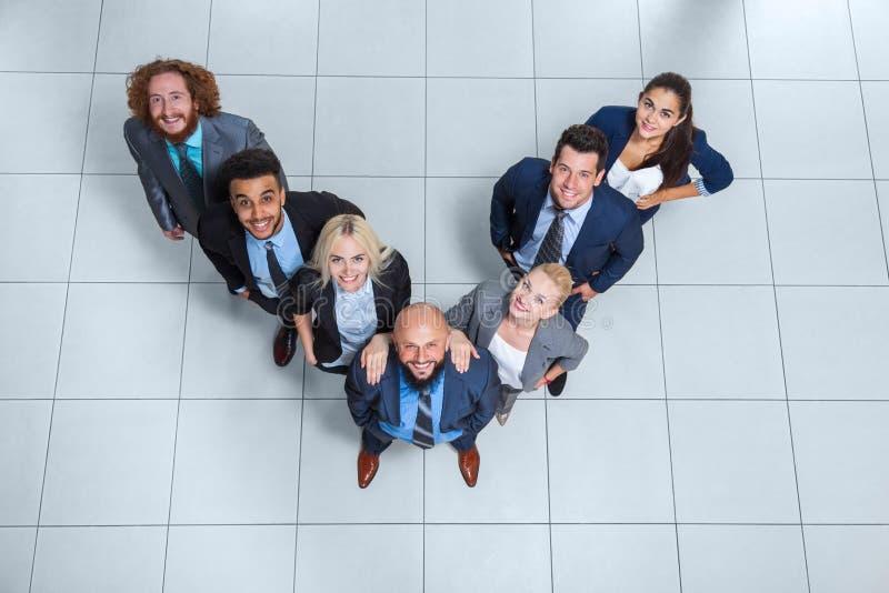 De bedrijfsmensen groeperen Gelukkige Glimlach die zich bij Moderne Bureau Hoogste Mening bevinden royalty-vrije stock foto's