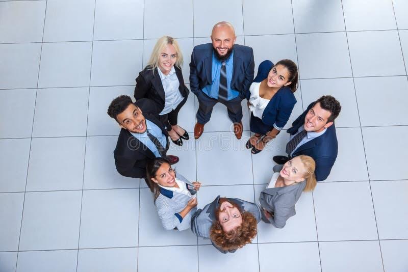 De bedrijfsmensen groeperen Gelukkige Glimlach die zich bij Moderne Bureau Hoogste Mening bevinden royalty-vrije stock afbeeldingen