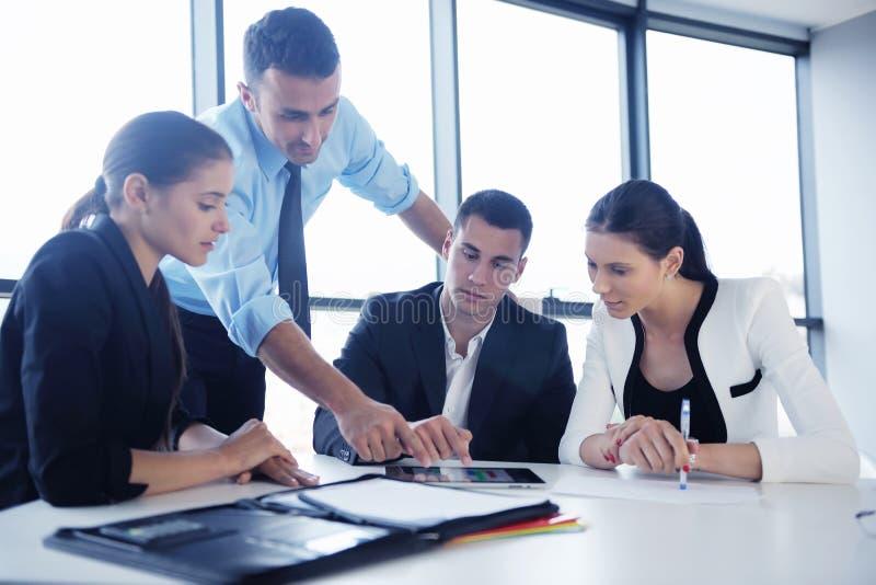 De bedrijfsmensen groeperen zich in een vergadering op kantoor stock afbeeldingen