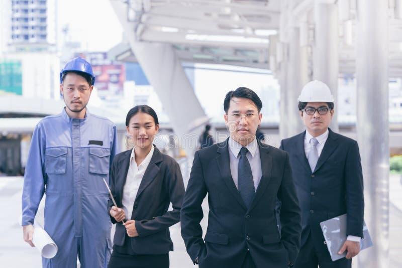 De bedrijfsmensen groeperen zich en het Teambeheer raadplegend de architect en de secretaresse die van de bouwingenieur met veili royalty-vrije stock afbeeldingen