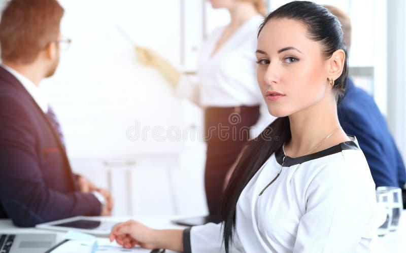 De bedrijfsmensen groeperen zich op vergadering in bureau Nadruk bij mooie vrolijke glimlachende onderneemster Collectieve confer royalty-vrije stock afbeelding