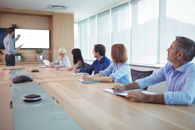 De bedrijfsmensen op conferentie dienen tijdens vergadering in stock afbeeldingen