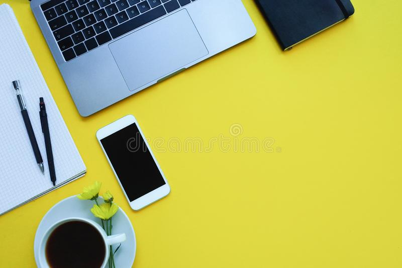 De bedrijfsvlakte legt: bureau met notitieboekje, potlood, kop van koffie op gele lijst stock afbeelding