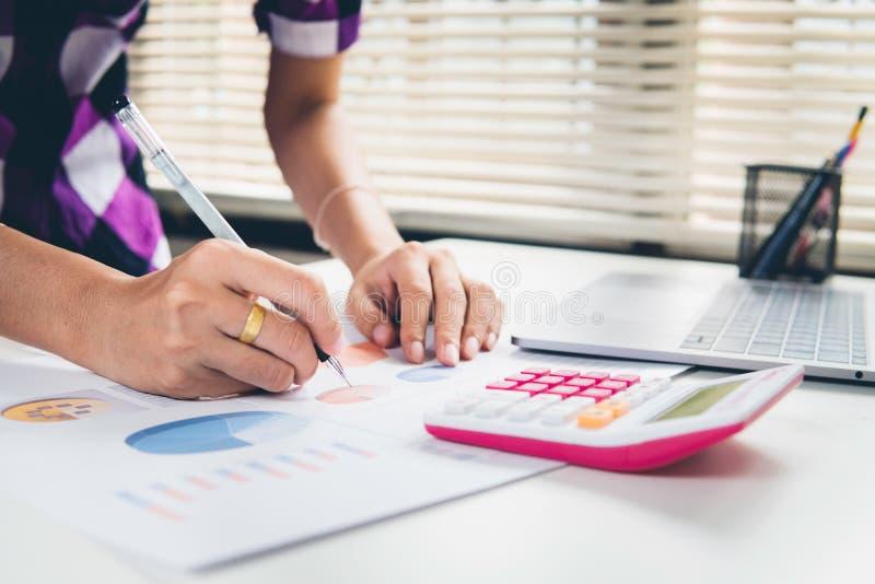 De bedrijfsvrouw berekent over kosten en het doen van financiën op kantoor royalty-vrije stock foto's