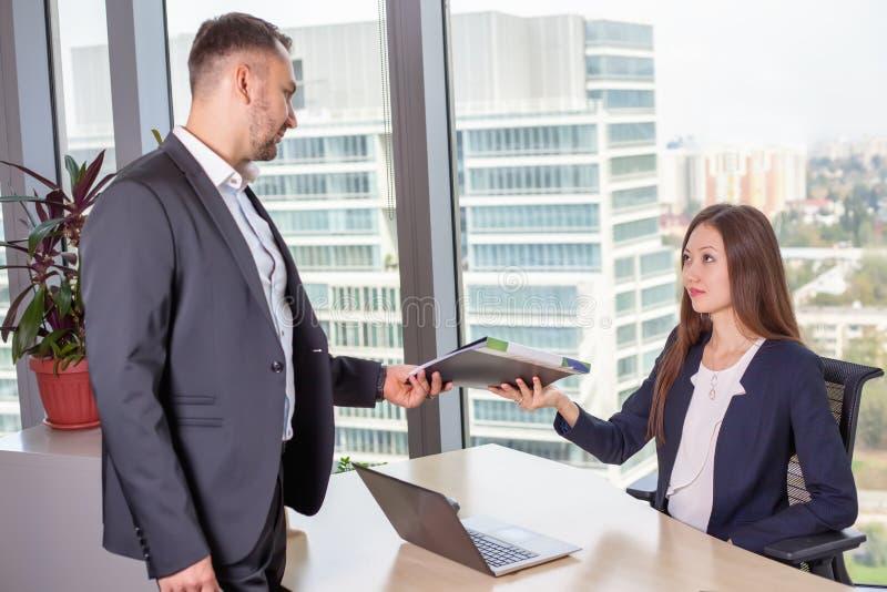 De bedrijfsvrouw bespreekt het rapport met zijn collega op het werk royalty-vrije stock afbeeldingen