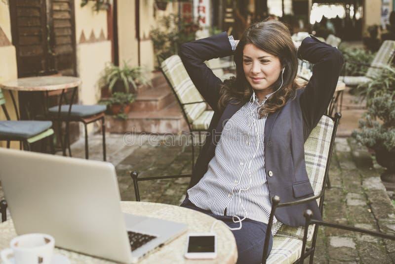 De bedrijfsvrouw bij koffie neemt een onderbreking van het werk Het luisteren muziek royalty-vrije stock fotografie