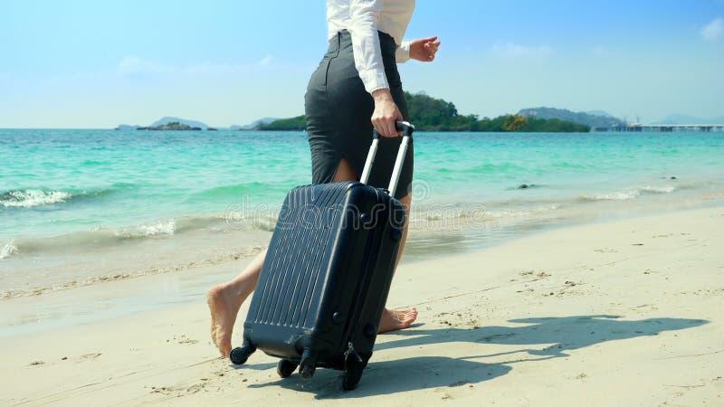 De bedrijfsvrouw in bureaukleren loopt blootvoets aan het overzees langs een wit zandig strand freelance, langverwachte vakantie royalty-vrije stock foto