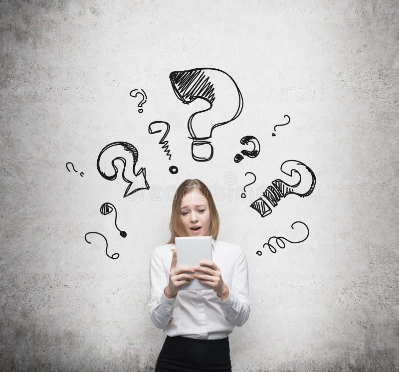 De bedrijfsvrouw denkt over ingewikkelde vragen Getrokken vraagtekens op de donkere muur stock afbeeldingen