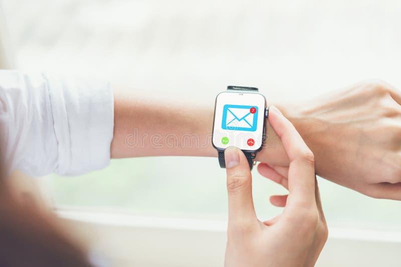 De bedrijfsvrouw die slim horloge met behulp van toont pictogram sociale e-mail, Concept mededeling en online het werken stock afbeelding