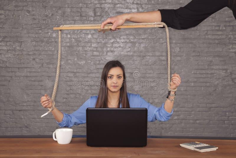 De bedrijfsvrouw is een marionet in de handen van een bedrijf stock foto
