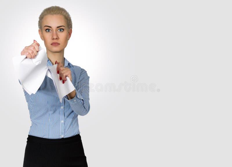 De bedrijfsvrouw in een Woede scheurt Document Op witte achtergrond stock foto