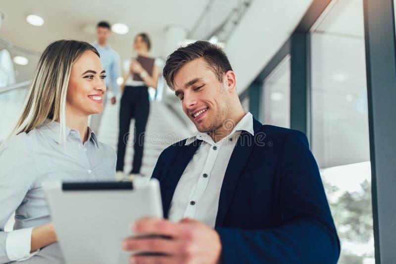 De bedrijfsvrouw en bemant hun holding een tablet in handen en het glimlachen bij de camera Op de achtergrond zijn bedrijfsmensen stock foto