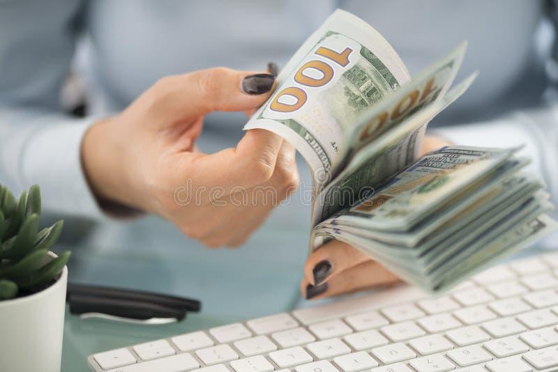 De bedrijfsvrouw, het tellen int ons dollars boven wit computertoetsenbord royalty-vrije stock fotografie